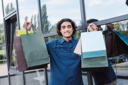 Photo pour Joyeux beau jeune homme tenant des sacs à provisions et souriant à la caméra - image libre de droit