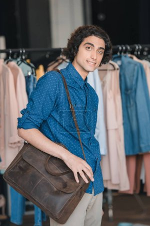Photo for Handsome young man with shoulder bag shopping in boutique - Royalty Free Image