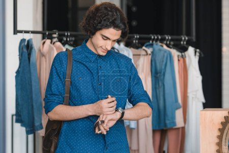 man choosing wristwatches in boutique