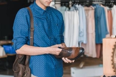 Photo pour Plan recadré de jeune homme tenant des chaussures tout en faisant du shopping en boutique - image libre de droit