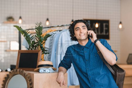 Photo for Smiling young man talking on smartphone while shopping in boutique - Royalty Free Image
