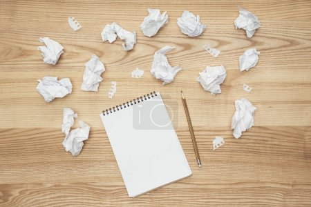 Photo for Top view of in empty notepad on wooden tabletop with crumpled papers - Royalty Free Image