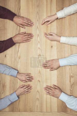 Photo pour Vue de dessus des mains des gens d'affaires sur la réunion sur la table en bois - image libre de droit