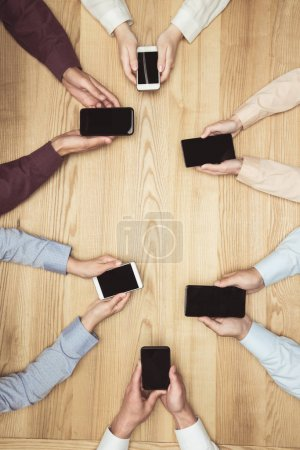Businesspeople with smartphones on meeting