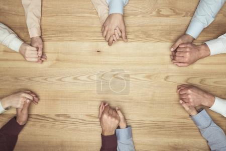 Top view of people holding hands on wooden tableto...