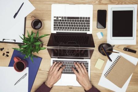 Photo pour Fournit une vue supérieure d'homme d'affaires travaillant et taper sur ordinateur portable au lieu de travail avec bureau et gadgets - image libre de droit