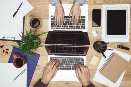 Photo for Top view of businesspeople working and typing on laptops at workplace with gadgets and office supplies - Royalty Free Image