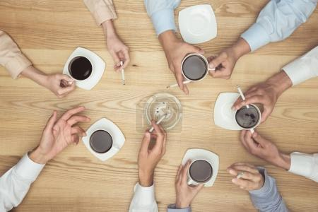 Photo for Top view of businesspeople smoking on coffee break on wooden tabletop - Royalty Free Image
