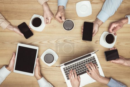 Photo for Top view of businesspeople on brainstorming with documents and laptop, smartphones, digital tablet and coffee at workplace - Royalty Free Image