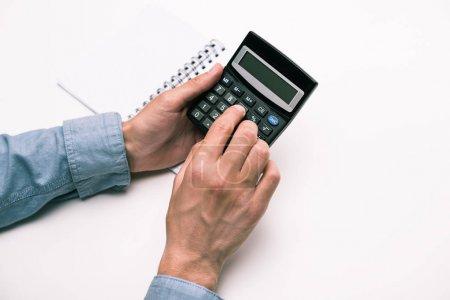 Photo pour Vue recadrée de mains mâles avec calculatrice et bloc-notes isolé sur blanc - image libre de droit