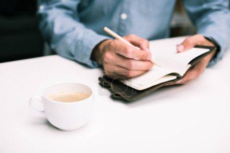 Photo pour Vue recadrée des mains masculines avec tasse de café écrit dans le journal - image libre de droit