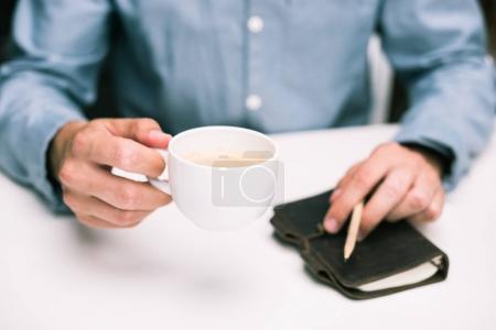 Photo pour Vue recadrée des mains masculines avec tasse à café et journal intime - image libre de droit