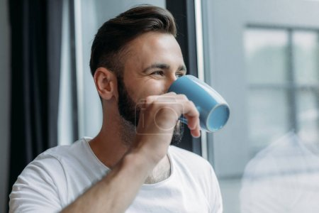 Photo for Handsome young man drinking tea from cup and looking at window at home - Royalty Free Image