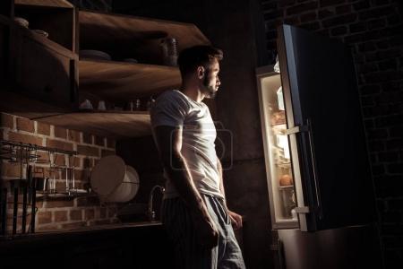 Looking at open refrigerator at night