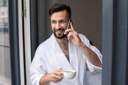 homme en peignoir parlant sur smartphone