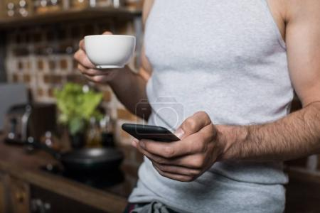 Man using smartphone while drinking coffee