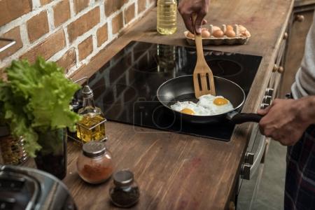 man preparing eggs for breakfast