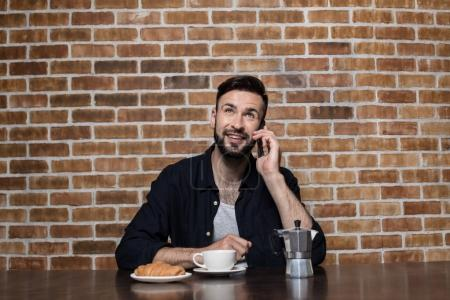 man using smartphone during breakfast