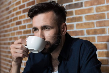 Bearded young man drinking coffee
