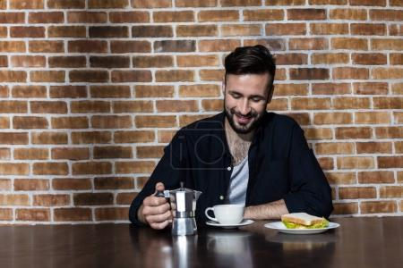 bärtiger junger Mann trinkt Kaffee