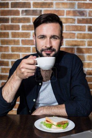 Mann trinkt Kaffee mit Sandwich
