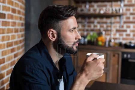 Photo pour Beau jeune homme barbu buvant du café le matin - image libre de droit