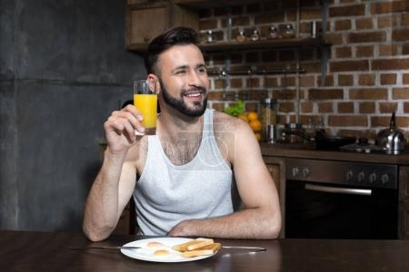Bearded young man drinking juice