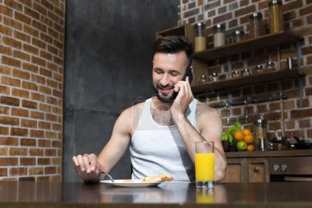 bearded young man eating breakfast