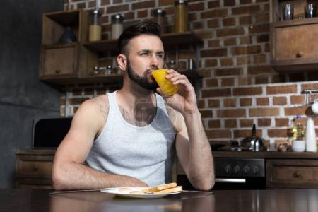 bärtiger junger Mann trinkt Saft
