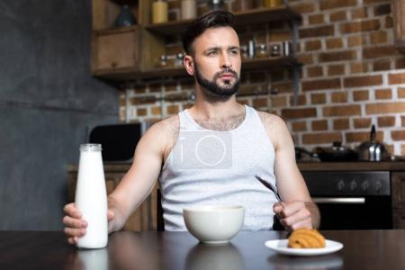 Thoughtful man with milk at breakfast