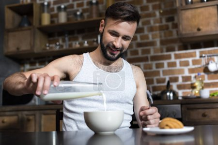Man pouring milk at breakfast