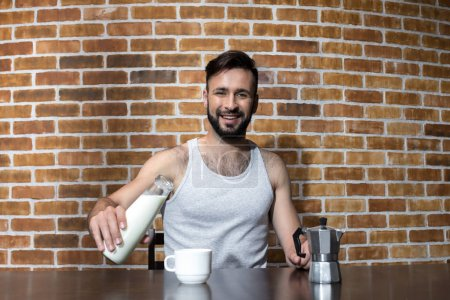 Young man pouring milk at breakfast