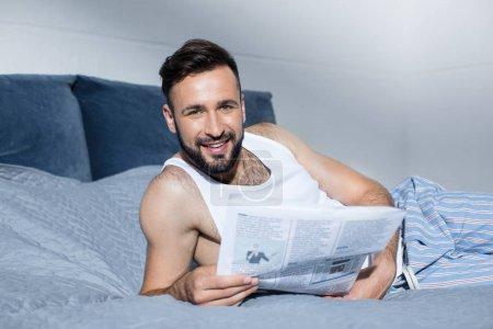 Photo pour Bel homme barbu lire journaux et souriant à la caméra en position couchée dans son lit - image libre de droit