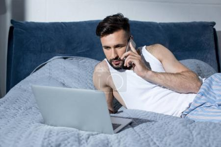 young man using gadgets in bed
