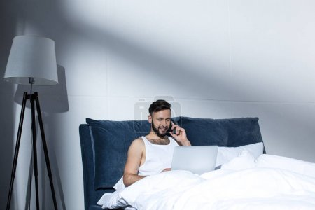 handsome man using gadgets in bed