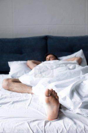 Photo pour Vue rapprochée du jeune homme endormi dans son lit sous la couverture blanche dans son lit - image libre de droit