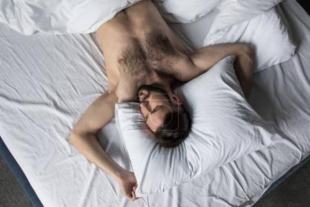 top view of man sleeping in bed
