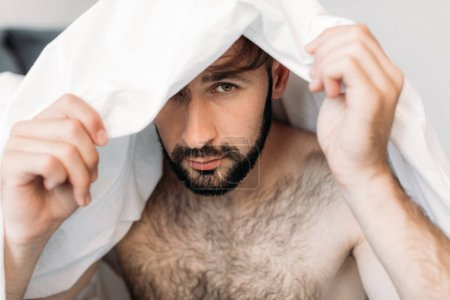 handsome shirtless man under blanket