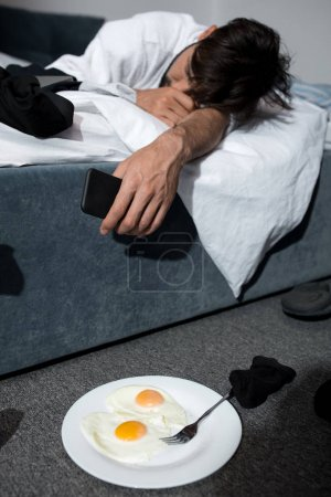 Photo for Tired young man in bathrobe sleeping on bed in morning - Royalty Free Image