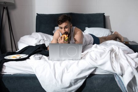 Photo for Bearded young man using laptop and eating sandwich while lying in bed at morning - Royalty Free Image