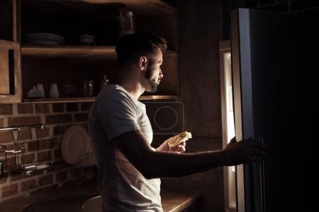 man in pajamas eating and looking at refrigerator