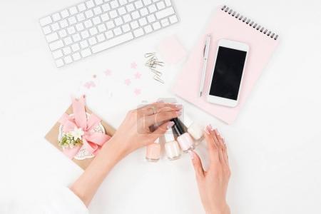 Photo pour Vue de dessus des mains féminines avec manucure belle tenue vernis à ongles sur lieu de travail - image libre de droit