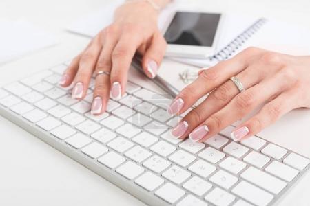 Photo pour Recadrée coup de jeune femme d'affaires avec manucure belle frappe sur le clavier au lieu de travail - image libre de droit