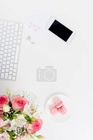 Photo for Top view of smartphone with blank screen, keyboard, macarons and flowers on white - Royalty Free Image