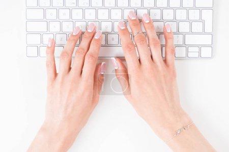 Photo pour Vue du haut des mains féminines avec une belle manucure tapant sur le clavier - image libre de droit