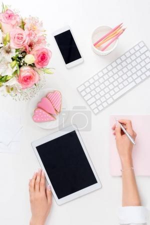 Photo pour Spectacle recadré de la femme en utilisant une tablette numérique et de prendre des notes sur le lieu de travail - image libre de droit