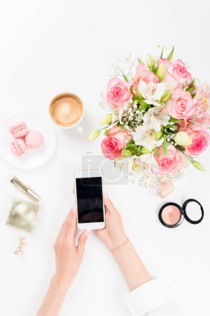 Photo for Cropped shot of woman using smartphone with blank screen near flowers. cosmetics and macarons - Royalty Free Image