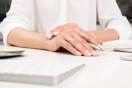 Female hands with pen at workplace