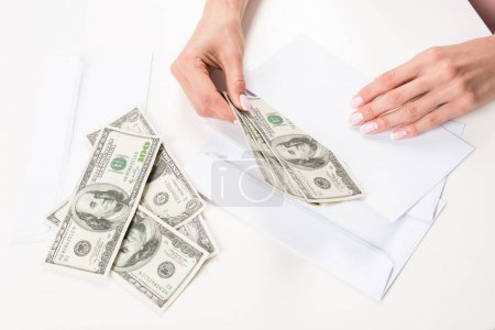 female hands with dollar banknotes in envelope