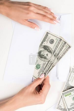 Photo for Top view of female hands holding envelope with dollar banknotes - Royalty Free Image